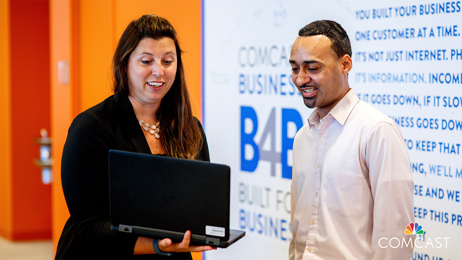 Woman showing a man something on her laptop as they stand in front of Comcast Business logo