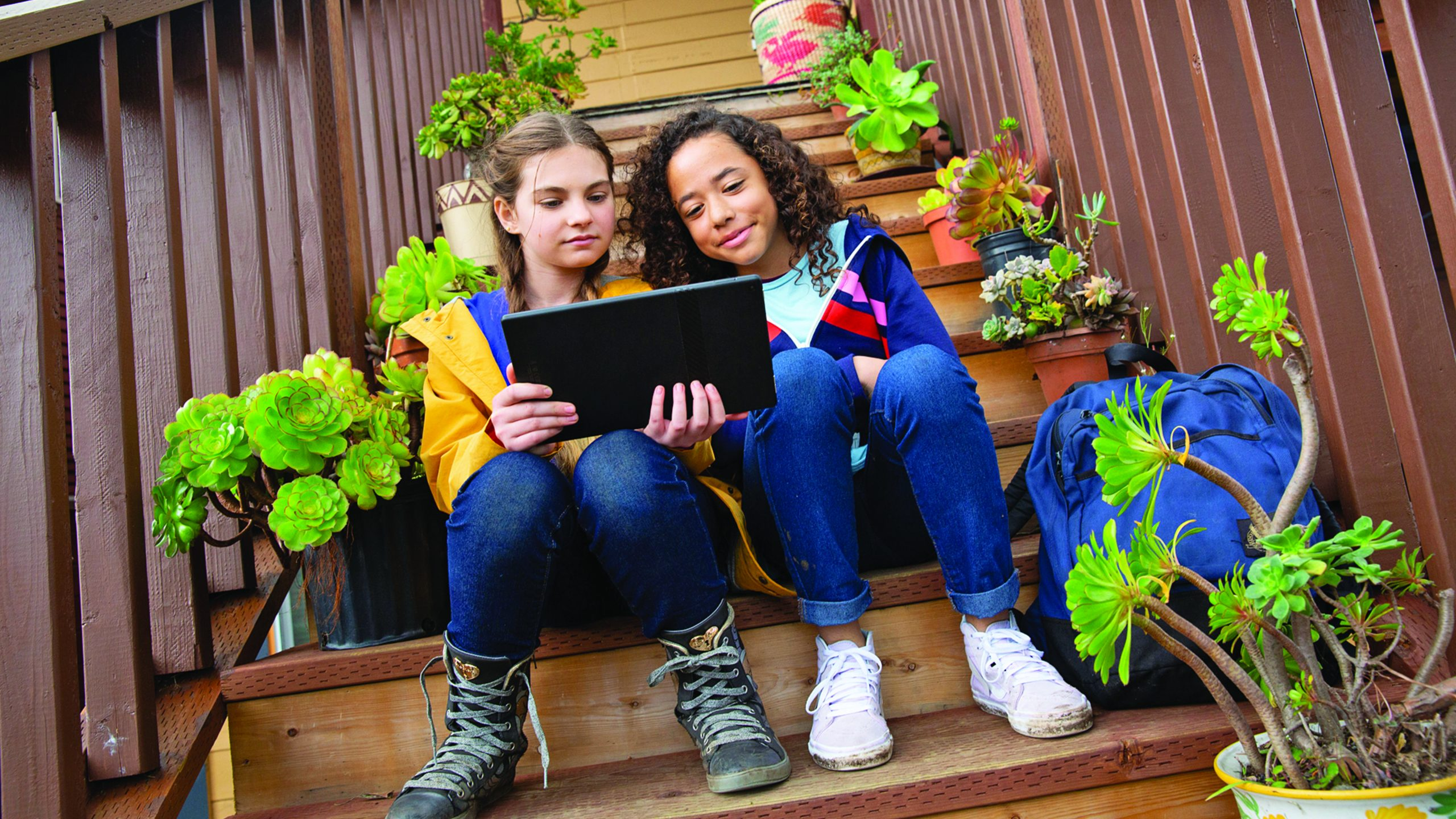 two girls sitting on outdoor steps, looking at a laptop screen
