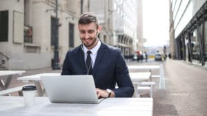 man typing on laptop outdoors