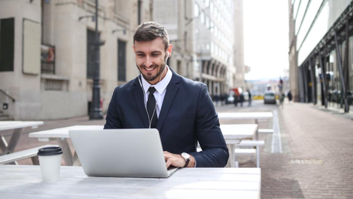 man typing on laptop outdoors